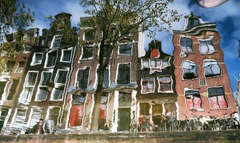 典型的狭窄的房子的反射有大窗口的在运河,阿姆斯特丹 库存图片