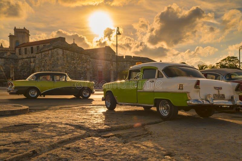 经典汽车在哈瓦那旧城照亮了在日落 免版税图库摄影