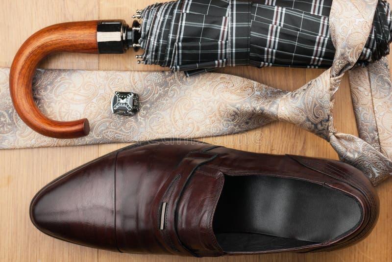 经典精神鞋子,领带,伞,在木地板上的链扣 免版税库存图片