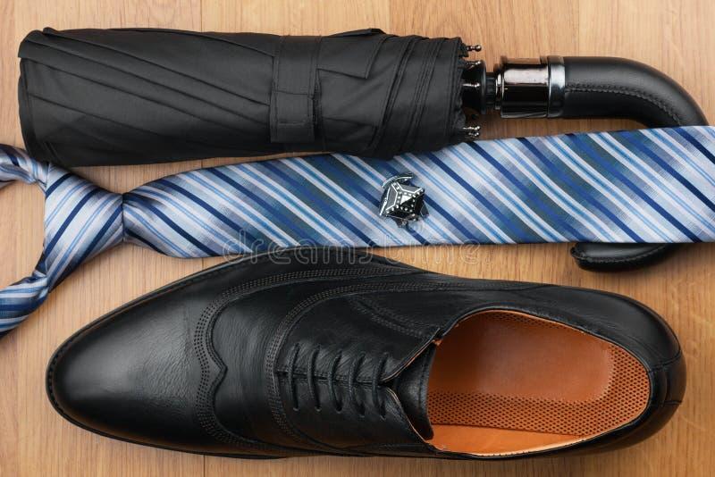 经典精神鞋子,领带,伞,在木地板上的链扣 库存照片