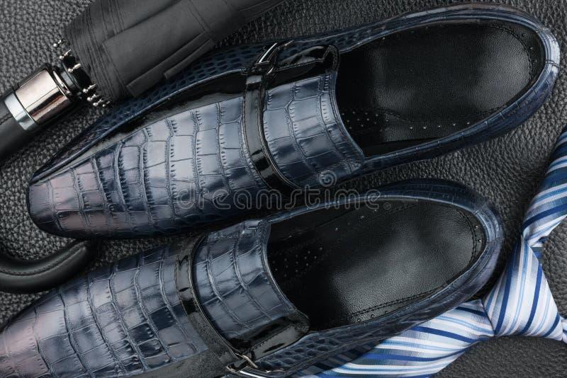 经典蓝色人的鞋子,领带,在黑皮革的伞 免版税库存照片
