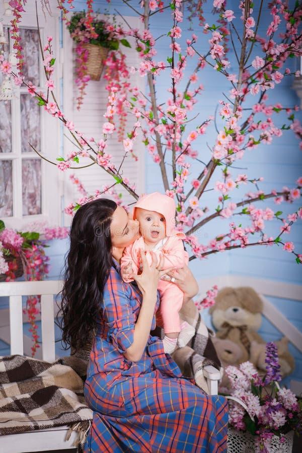经典衣服的美丽的企业夫人使用与她的甜矮小的婴孩 免版税库存图片