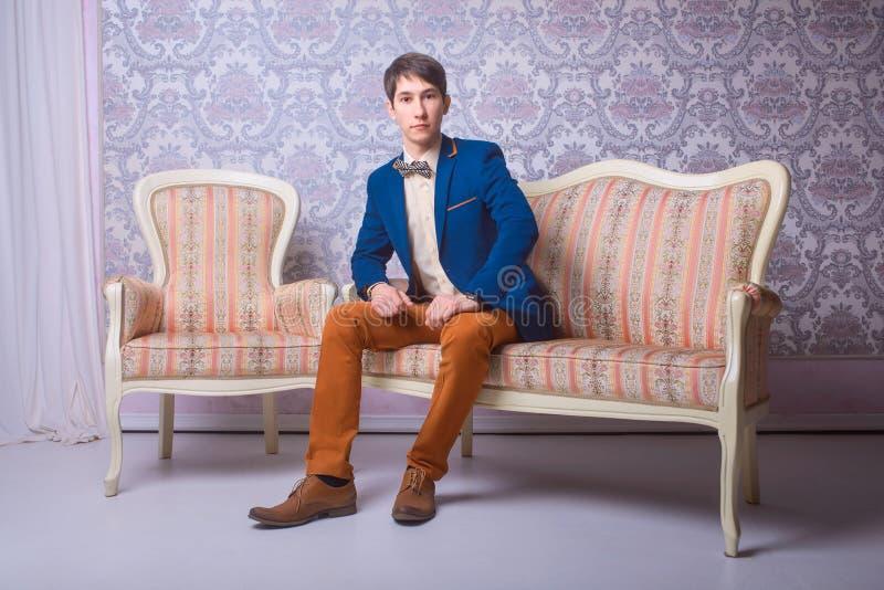 经典衣服的年轻人坐长沙发 免版税图库摄影