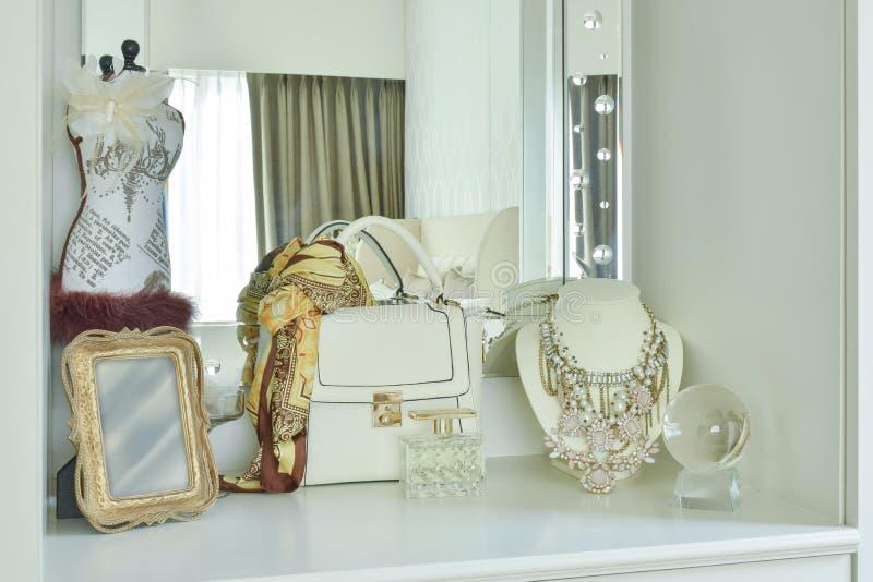 经典袋子和美丽的项链在白色梳妆台上 免版税图库摄影