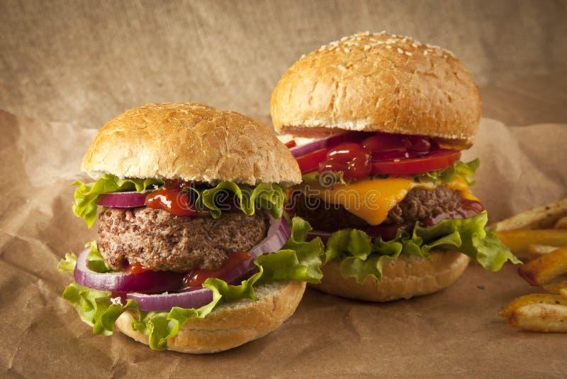 经典豪华乳酪汉堡用莴苣、葱、蕃茄和腌汁在芝麻籽小圆面包 免版税库存照片