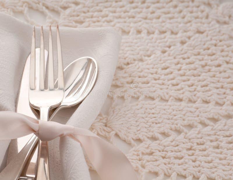 典雅与叉子、匙子和刀子在奶油色布料餐巾和桌布银器的白色桌餐位餐具与室或 免版税图库摄影
