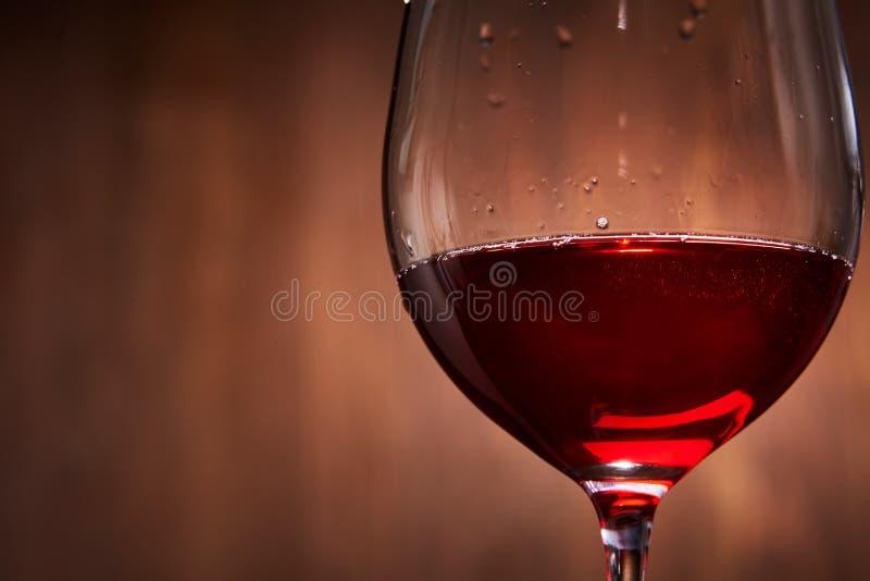 典雅和易碎的葡萄酒杯反对棕色木背景特写镜头的鲜美红葡萄酒 免版税库存图片
