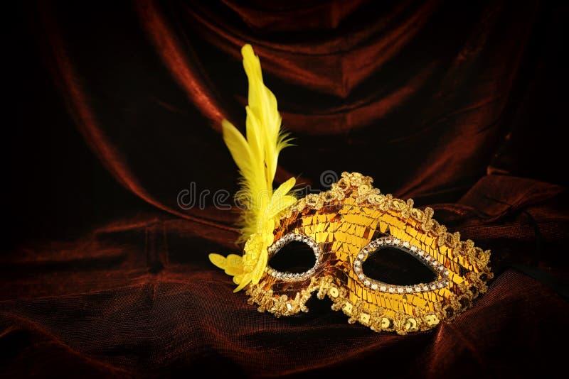 典雅和精美在黑暗的天鹅绒和丝绸背景的金威尼斯式面具照片  库存照片