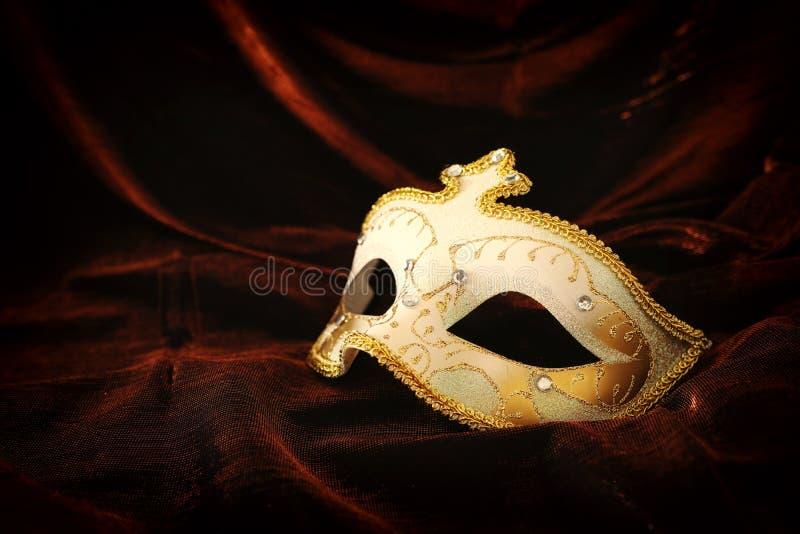 典雅和精美金子,在黑暗的天鹅绒和丝绸背景的白色威尼斯式面具照片  免版税库存图片