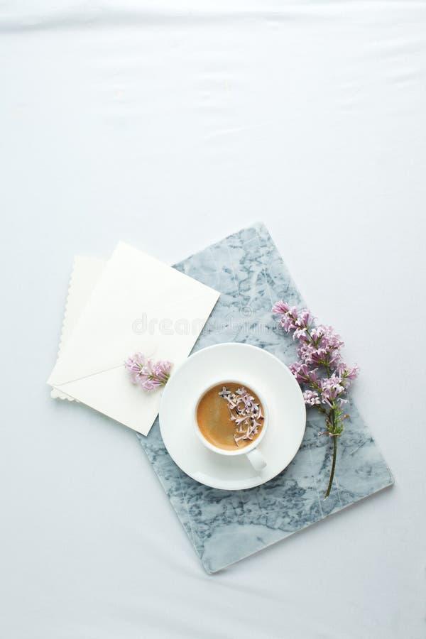 典雅妇女的桌面 在大理石板材的咖啡杯和ililac分支在白色桌 艺术品的大模型 o 库存照片