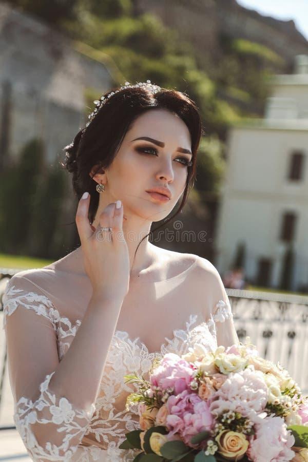 典雅婚礼礼服摆在的新娘室外与嫩bouque 免版税库存图片