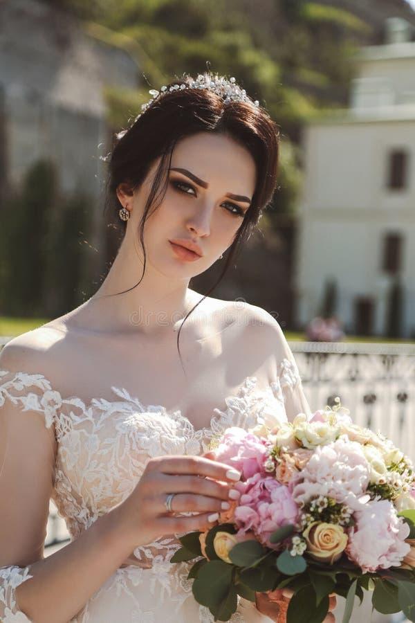 典雅婚礼礼服摆在的新娘室外与嫩bouque 库存图片