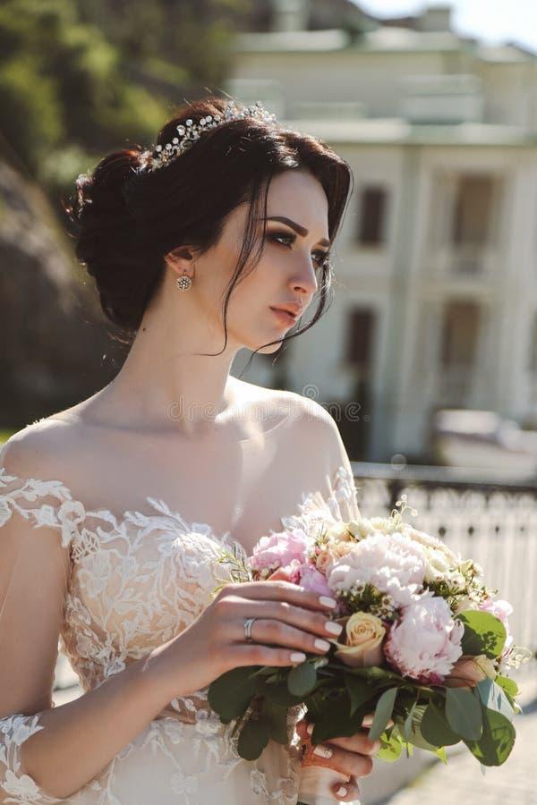 典雅婚礼礼服摆在的新娘室外与嫩bouque 库存照片