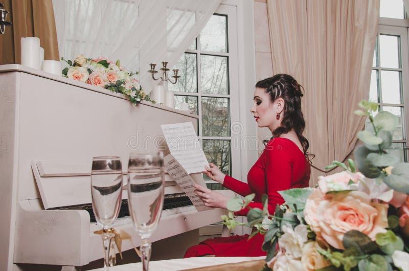 典雅平衡的红色礼服浅黑肤色的男人30-35岁妇女钢琴演奏家在减速火箭的钢琴,看坐音符  免版税库存照片