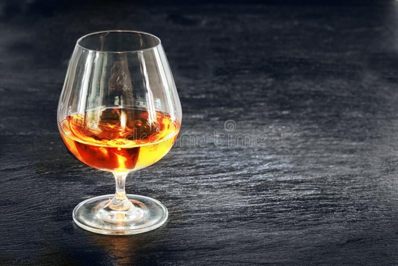 典雅的一口威士忌酒用发光的金黄科涅克白兰地 免版税库存照片