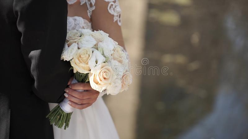 典雅的一起摆在户外在一婚礼之日的新娘和新郎 拿着白色玫瑰花束的新娘,当站立时 免版税库存照片