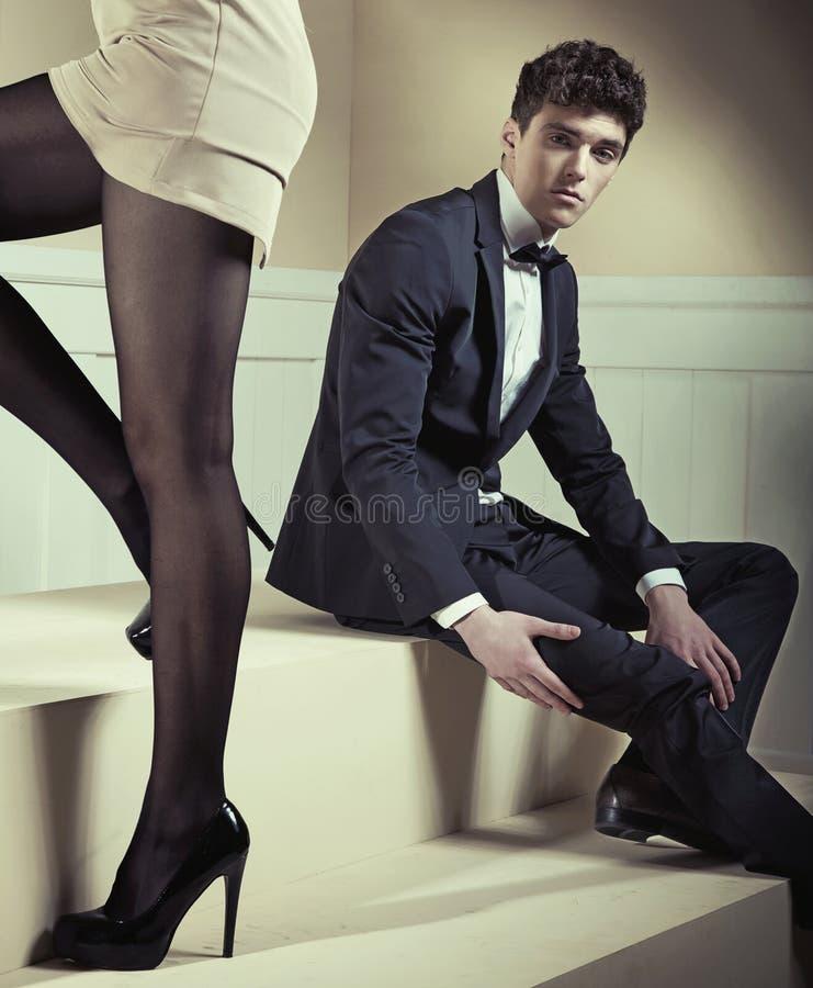 年轻典雅的人坐台阶 免版税图库摄影