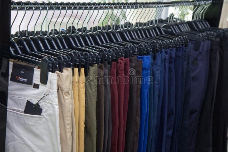 典雅的人衣物在商店,许多裤子典雅的礼服,绅士样式,秋天春天婚礼穿衣 库存图片