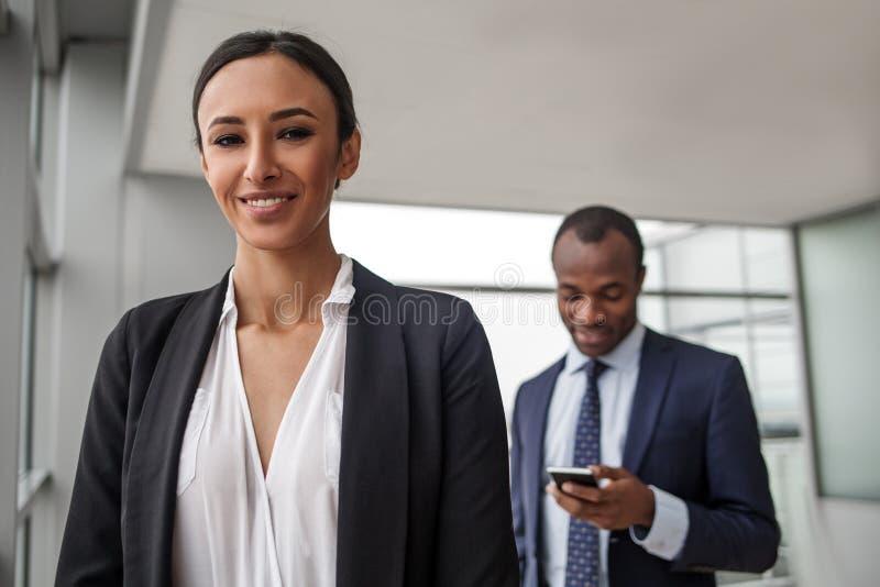 典雅的企业家微笑着,当摆在与伙伴时 库存图片