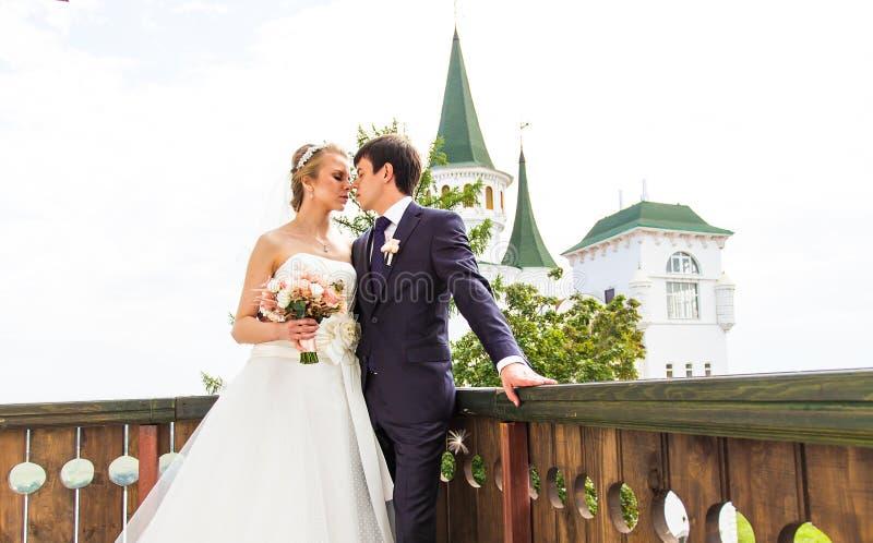 典雅的华美的愉快的站立在阳台的新娘和新郎 免版税图库摄影