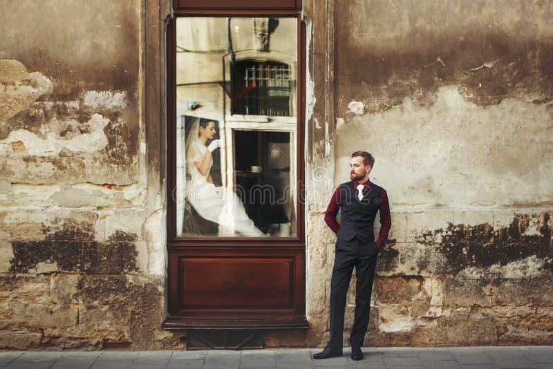 典雅的华美的新娘饮用的咖啡在窗口和时髦的gr里 免版税库存照片