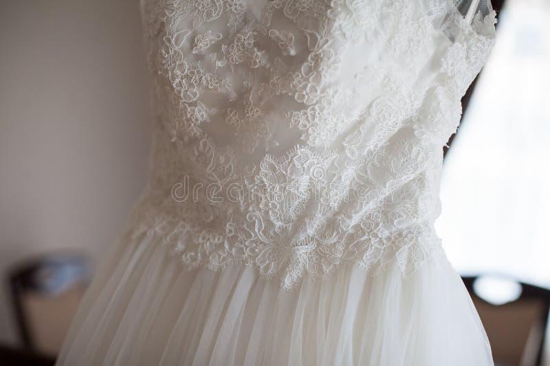 典雅的在一个挂衣架的葡萄酒白色礼服在豪华旅馆室 库存照片