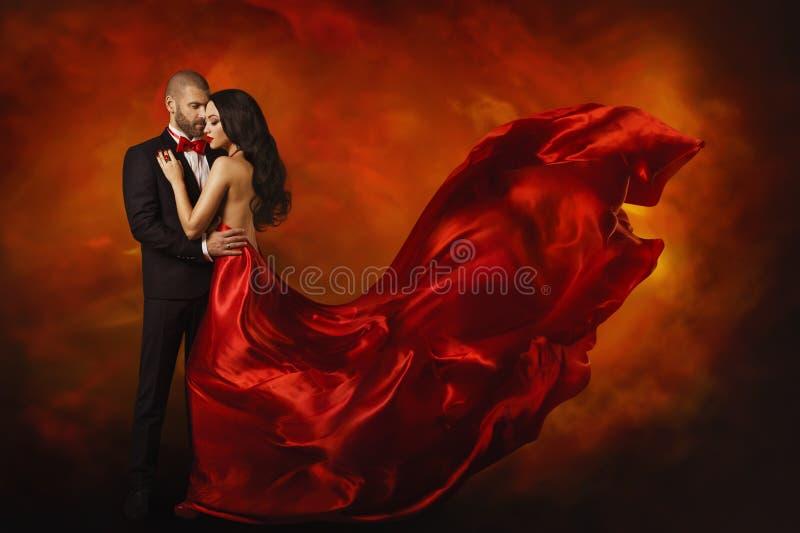 典雅的夫妇,红色礼服的跳舞的妇女有人的 图库摄影