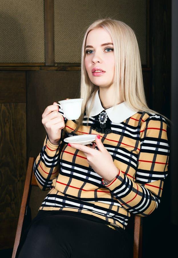 典雅的夹克的美丽的魅力blondie妇女有晚上构成的、坐的和饮用的咖啡或者茶 库存图片