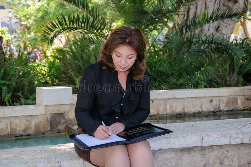 年轻典雅的女商人写入她的在同水准的笔记薄 免版税图库摄影