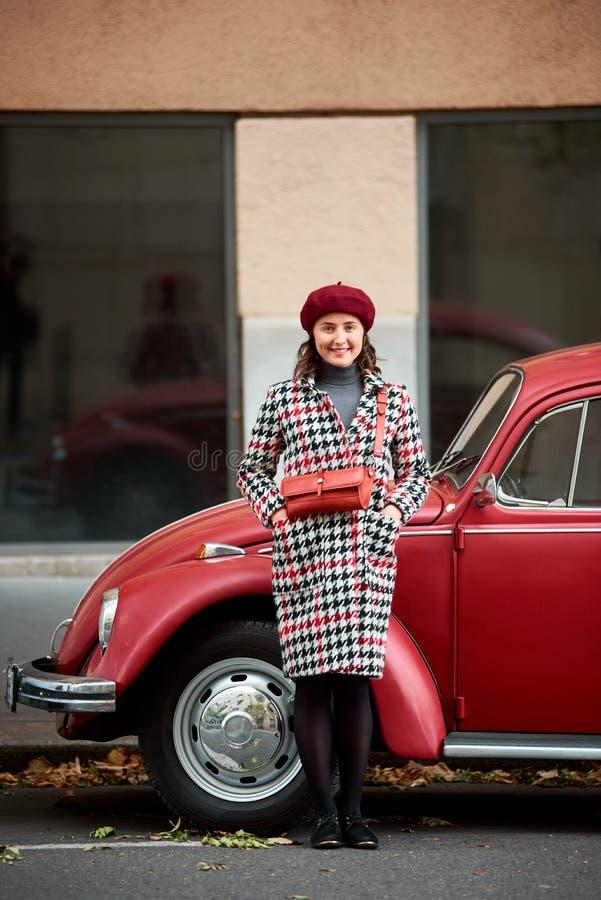 典雅的女孩在红色减速火箭的汽车附近摆在 户外,秋天城市 免版税库存图片