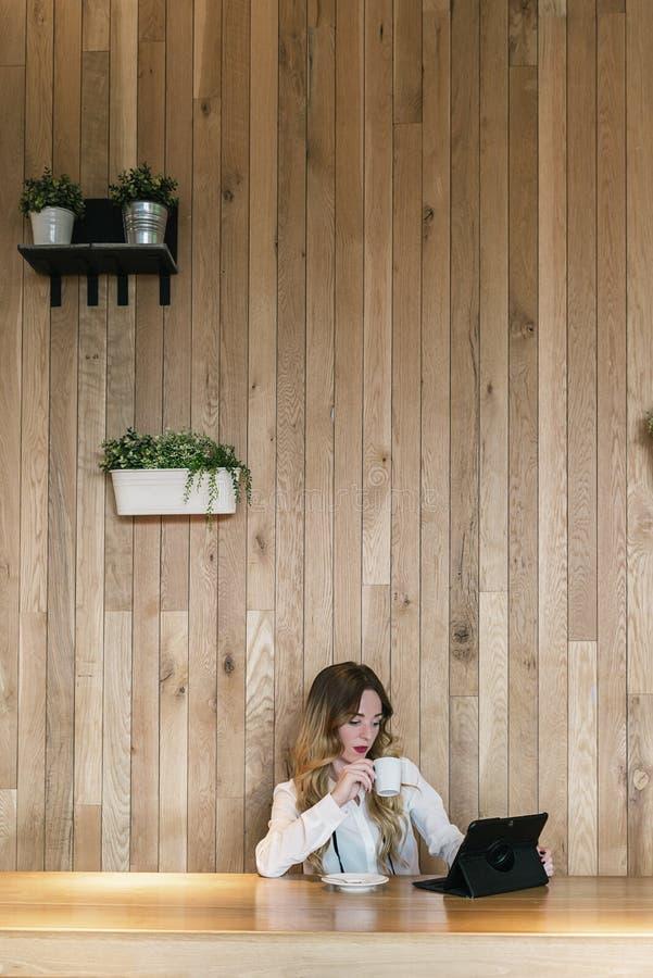 典雅的女实业家与一种片剂一起使用在餐馆 免版税图库摄影