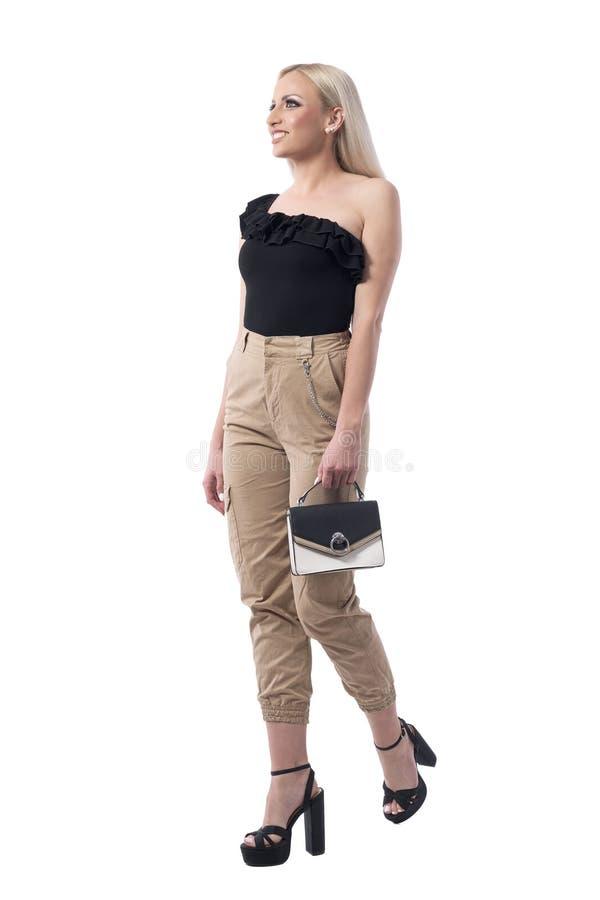 典雅的女性微笑和走与提包的魅力年轻金发妇女 图库摄影