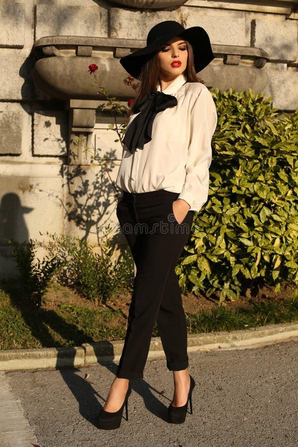戴典雅的女衬衫、裤子和帽子的美丽的如贵妇妇女 免版税图库摄影