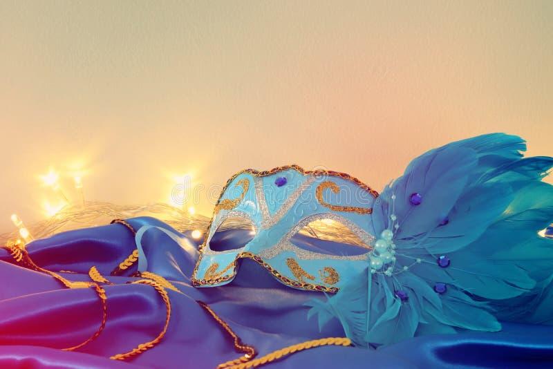 典雅的威尼斯式面具的图象在蓝色丝绸背景的 库存照片