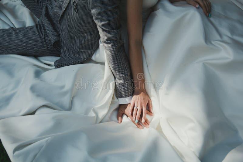典雅的婚姻的夫妇坐白色缎礼服 库存图片