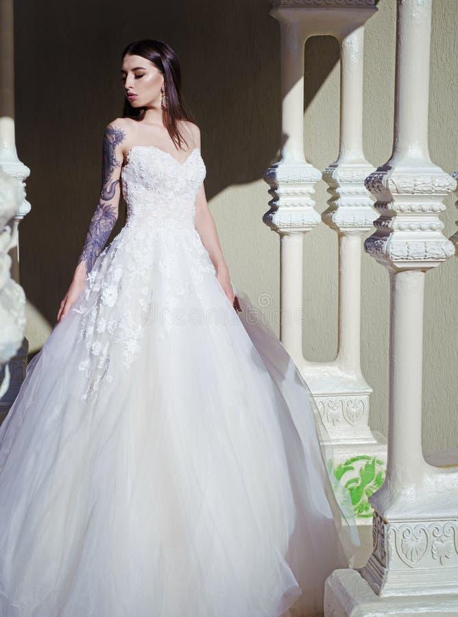 典雅的婚礼沙龙等待新娘 妇女为婚姻做准备 在精品店的美丽的婚纱 愉快 库存图片