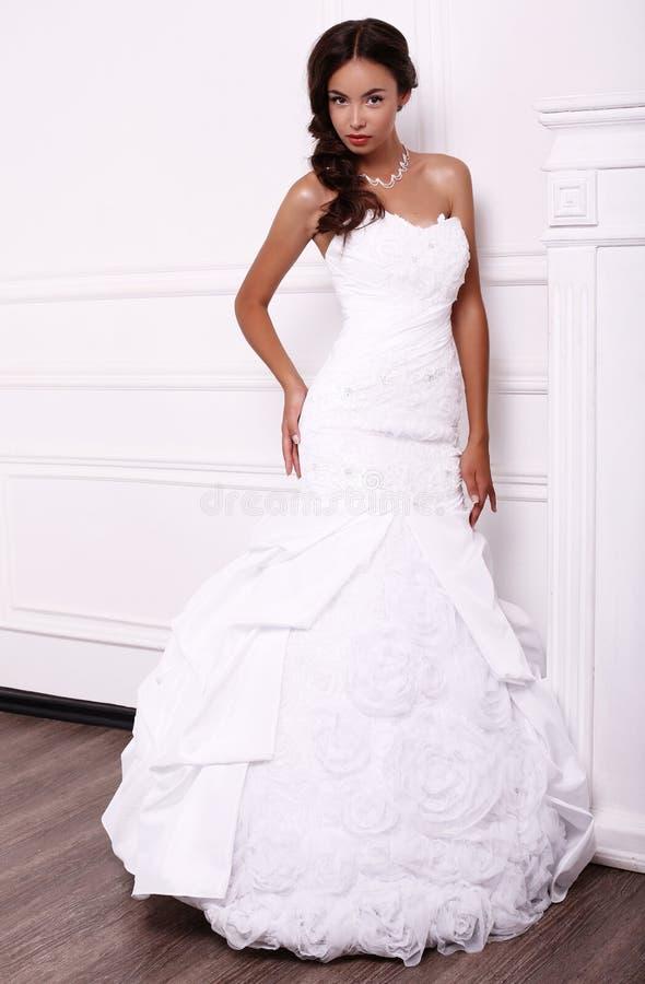 典雅的婚礼礼服的美丽的年轻新娘 免版税库存照片