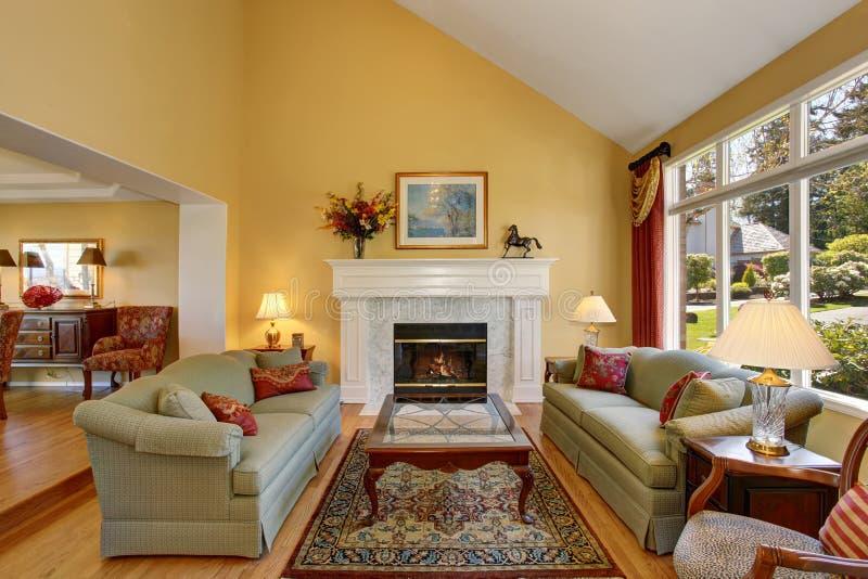典雅的客厅内部 有红色枕头和白色壁炉的灰色沙发创造舒适 库存图片