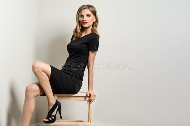 典雅的少妇白肤金发在黑礼服 免版税库存图片