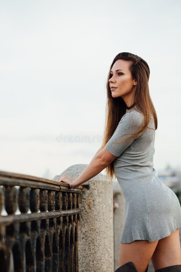 典雅的性感的女孩沿散步走 美丽的扶手栏杆,伪造 长期头发 免版税库存照片