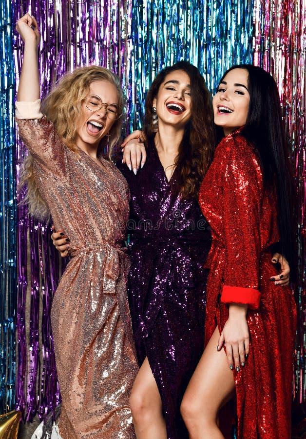 典雅的成套装备的庆祝新年的三名美丽的时髦的妇女的疯狂的党时间,生日,获得乐趣,跳舞 库存照片