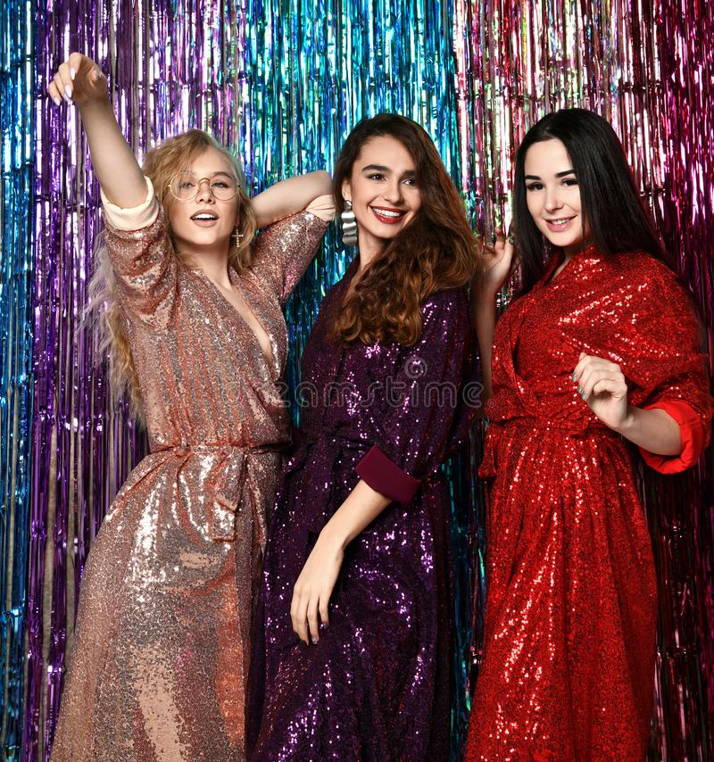典雅的成套装备的庆祝新年的三名美丽的时髦的妇女的疯狂的党时间,生日,获得乐趣,跳舞 免版税库存图片