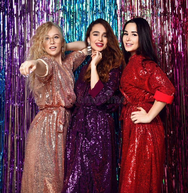 典雅的成套装备的庆祝新年的三名美丽的时髦的妇女的疯狂的党时间,生日,获得乐趣,跳舞 免版税库存照片