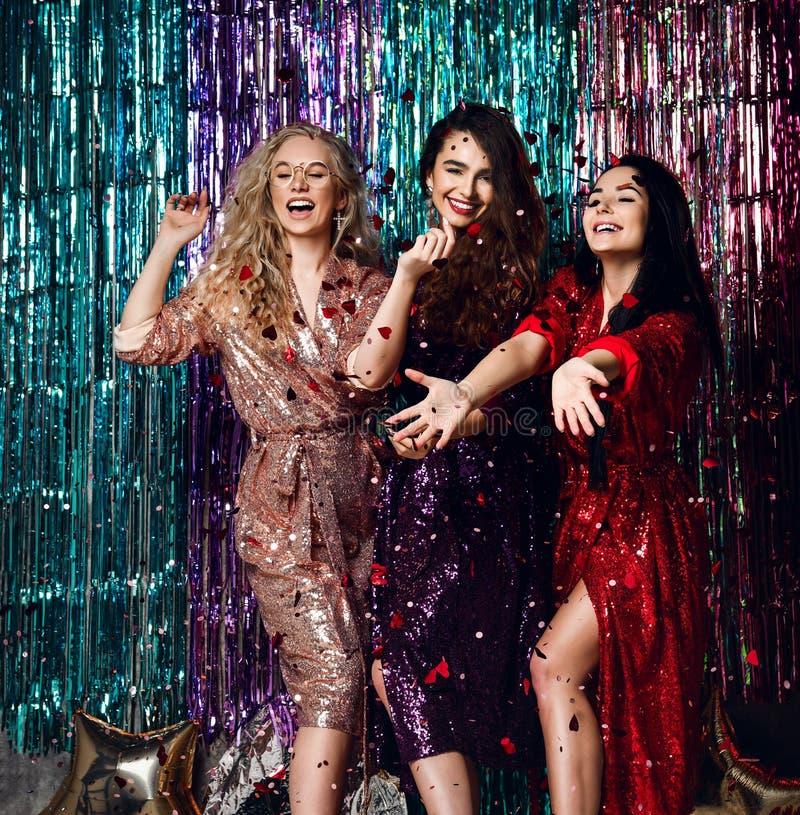 典雅的成套装备的庆祝新年,生日的三名美丽的时髦的妇女的党时间,获得乐趣,跳舞 免版税库存照片