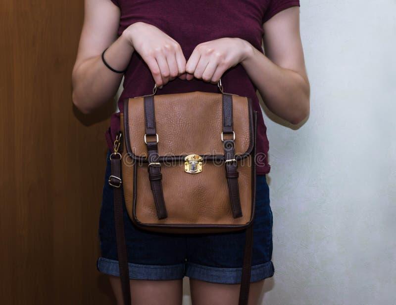 典雅的成套装备 棕色皮包提包特写镜头在手中时髦的妇女时兴的女孩 免版税库存照片