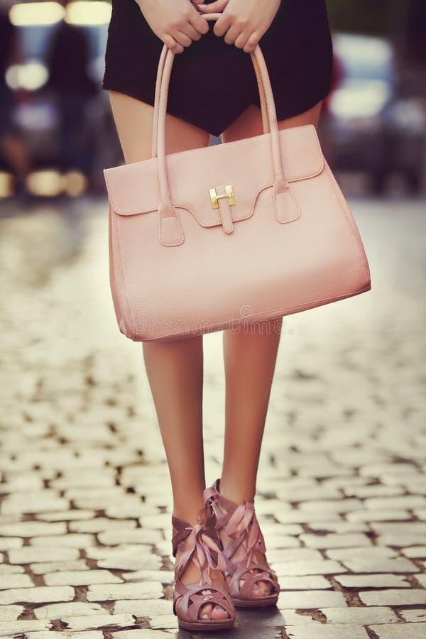 典雅的成套装备 特写镜头 皮包在时髦的妇女的手上 摆在街道上的时兴的女孩 女性方式 库存图片