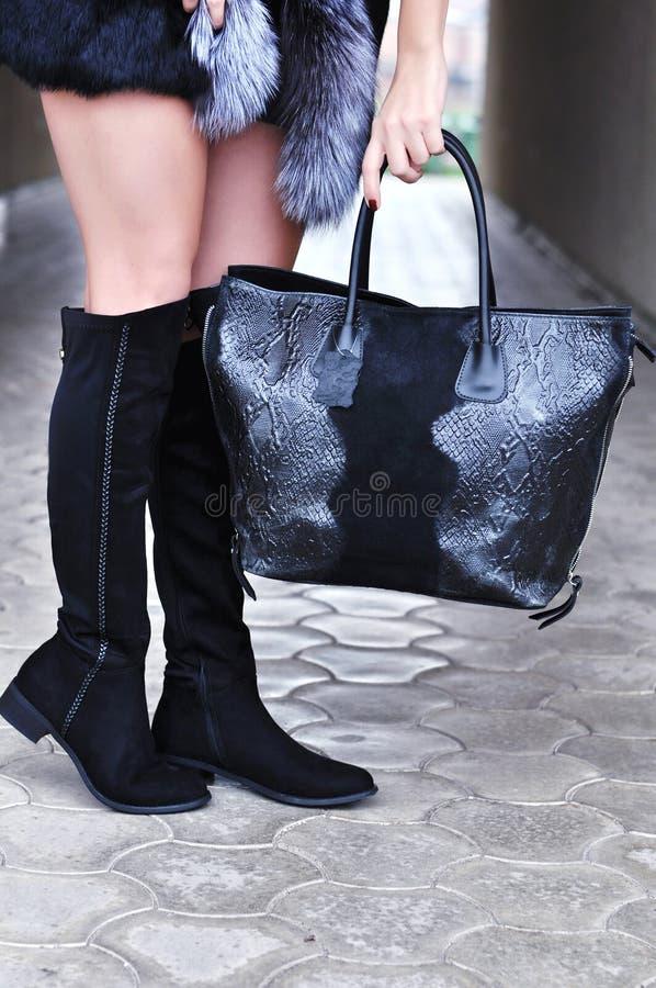 典雅的成套装备 年轻时髦的妇女走在秋天的,冬天城市,冷的季节,佩带的高跟的黑起动,绒面革黑袋子 库存照片