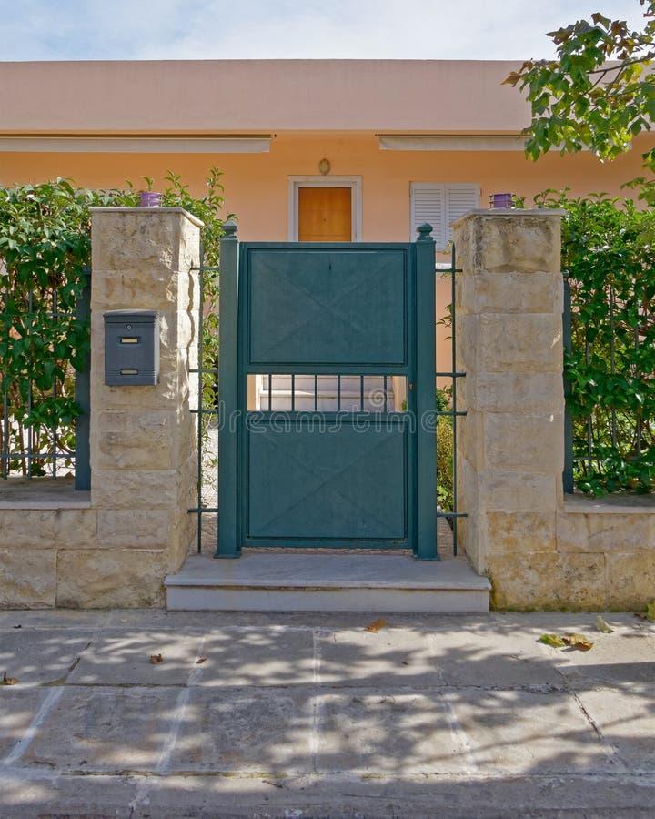 典雅的房子外在绿色金属门和棕色石被盖的专栏 库存照片