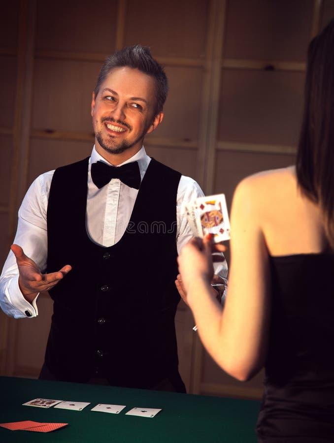 典雅的打扑克的经销商微笑的女孩 库存图片