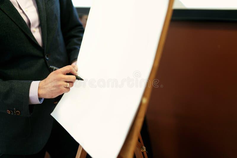 典雅的报告人讲师递拿着标志和写在emp 免版税库存图片